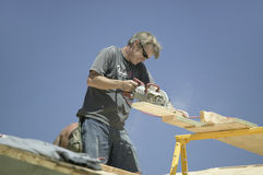 Carpenter sawing board on roof Stock Photos
