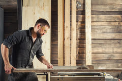 Carpenter sawing board. Young man builder carpenter sawing board with circular saw in workshop Royalty Free Stock Image