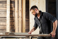 Carpenter sawing board. Young man builder carpenter sawing board with circular saw in workshop Royalty Free Stock Photos