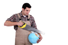 Carpenter sawing into globe Stock Photography