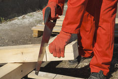Carpenter sawing lumber Stock Photography