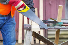 Carpenter sawing plank Stock Photos