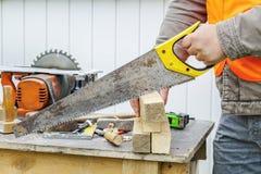 Carpenter sawing timber Stock Image