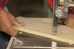 Carpenter sawing. Wood board on band saw Royalty Free Stock Image