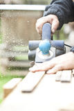 Carpenter sawing wood board Stock Photo
