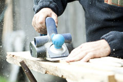 Carpenter sawing wood board Royalty Free Stock Photography
