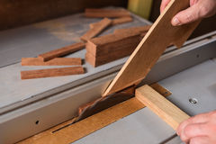 Carpenter sawing wood detail on circular saw hepling with stick Stock Images