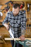 Carpenter sawing wood with hand saw in workshop Royalty Free Stock Photography