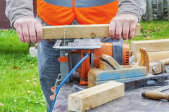 Carpenter sawing wooden plank with circular saw Royalty Free Stock Photography