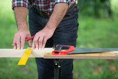 Carpenter sawing a wooden square with a wood saw Stock Photo