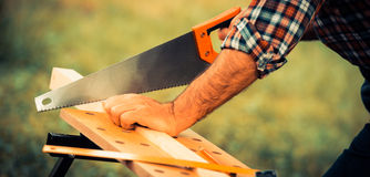 Carpenter sawing a wooden square with a wood saw Royalty Free Stock Images