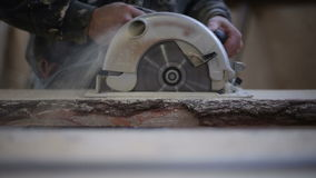 A carpenter saws off a board with a disk saw stock video footage
