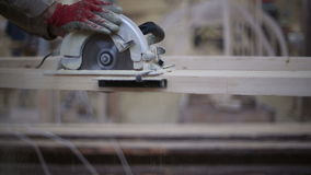 A carpenter saws off a board with a disk saw stock footage