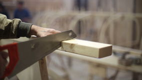 The carpenter saws off the wooden block with a hand hacksaw stock video