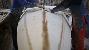 The carpenter seals the joints of the boat at the shipyard stock footage
