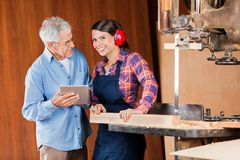 Carpenter With Senior Colleague Using Digital Royalty Free Stock Photos