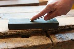 Carpenter sharpens a chisel stock image