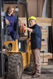 Carpenter Showing Something To Colleague In. Senior carpenter showing something to colleague sitting in forklift at workshop Royalty Free Stock Image