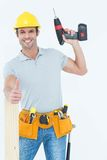 Carpenter showing thumbs up while holding drill machine. Portrait of happy male carpenter showing thumbs up while holding drill machine over white background stock photos