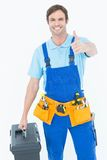 Carpenter showing thumbs up sign while carrying tool box Stock Image