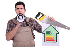 Carpenter with a sign. Carpenter with an energy rating sign royalty free stock photography