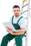 Carpenter sitting on ladder using laptop Royalty Free Stock Photo