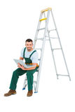 Carpenter sitting on ladder using laptop Royalty Free Stock Photography