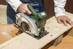 Carpenter slashes the board using an electric saw Royalty Free Stock Photos