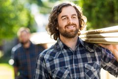 Carpenter Smiling While Carrying Planks With The Royalty Free Stock Images