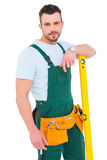 Carpenter smiling to camera with spirit level Royalty Free Stock Photo