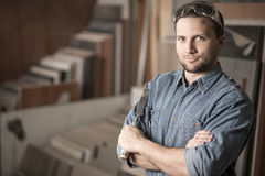 Carpenter standing with a chisel. Skilled adult carpenter standing with a chisel Stock Photo