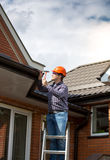 Carpenter standing on high ladder and repairing house roof Royalty Free Stock Photo