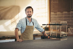 Carpenter standing proudly alongside a display case he is making Stock Photo