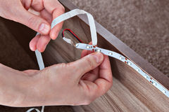 Carpenter sticks led tape inside furniture, close-up of hands. Stock Images