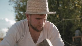 Carpenter in the straw hat hammers stock video footage