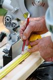Carpenter take notes on a wooden board before cutting Stock Photos
