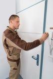 Carpenter Taking Measurement Of Door Royalty Free Stock Photos