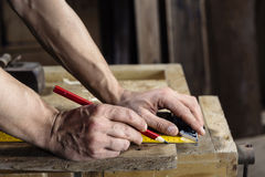 Carpenter taking measurement of a wooden plank Royalty Free Stock Photography