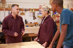 Carpenter Talking To Apprentices In Carpentry Workshop Stock Photos