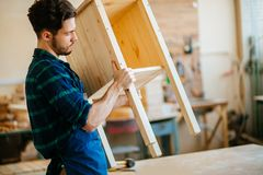 Carpenter testing wood plank evenness at workshop. Profession, carpentry, woodwork and people concept - young carpenter testing wood plank evenness at workshop Royalty Free Stock Image