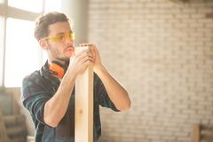 Carpenter testing wood plank evenness at workshop. Profession, carpentry, woodwork and people concept - young carpenter testing wood plank evenness at workshop Stock Photo