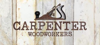 Carpenter text with planer on wooden background Royalty Free Stock Photo