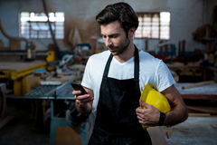Carpenter texting someone and holding his helmet Royalty Free Stock Photos