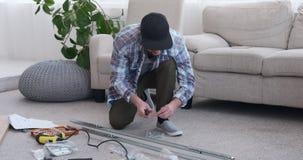Carpenter tightening screw on metal frame at home. Young carpenter tightening screw using screwdriver on metal frame at home stock footage