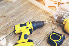 Carpenter tool. Wireless electric drill with screw and Measuring tape on wooden table,diy at home concept Royalty Free Stock Images