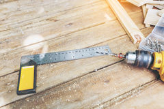 Carpenter tool. Wireless electric drill with screw and try square on wooden table,diy at home concept Stock Photo