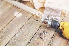 Carpenter tool. Wireless electric drill with screw on wooden table,diy at home concept Royalty Free Stock Photo