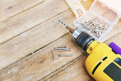 Carpenter tool. Wireless electric drill with screw on wooden table,diy at home concept Royalty Free Stock Images