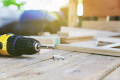 Carpenter tool. Wireless electric drill with screw on wooden table,diy at home concept Stock Image