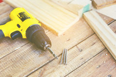 Carpenter tool. Wireless electric drill with screw on wooden table,diy at home concept Stock Photo